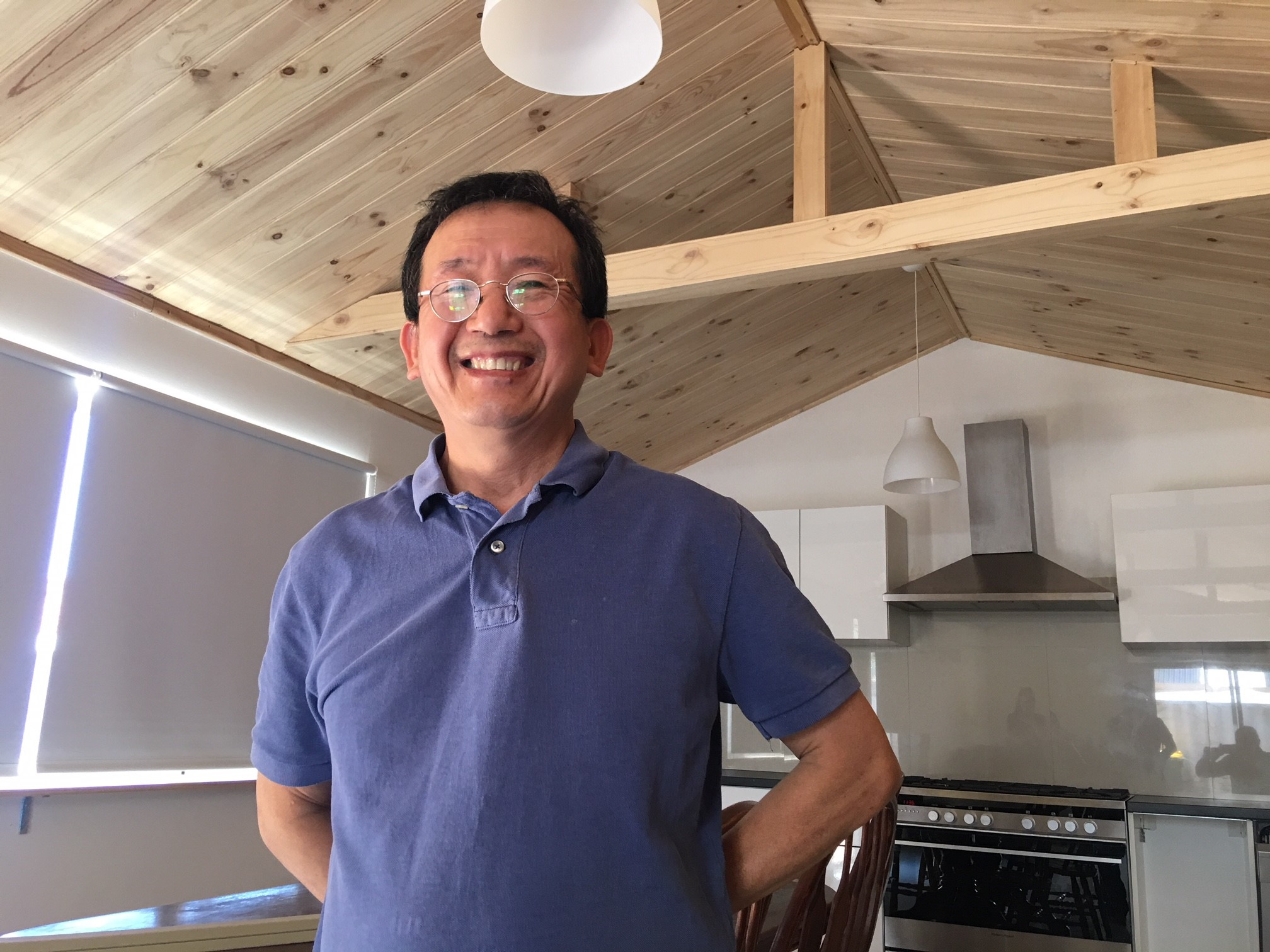 Dr Ba Huynh Pham smiling at his timber-lined ceiling in a room in his home