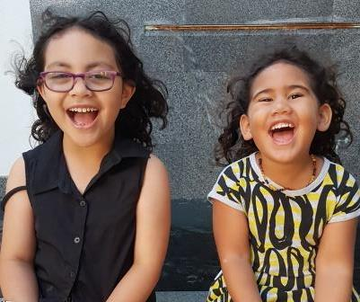 The picture shows Paisley and Olive, two small girls, sitting next to each other with big smiles on their faces.