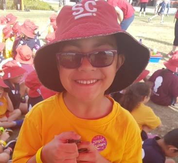 Paisley, aged 5, is dressed in her sports uniform and is wearing a hat and sunglasse. The photo was taken at the cross country event.