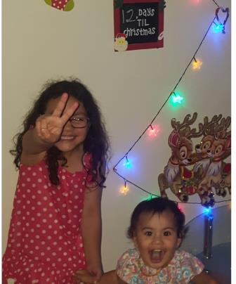Paisley and her younger sister Parker stand in front of a wall with lights shaped into a Christmas tree.