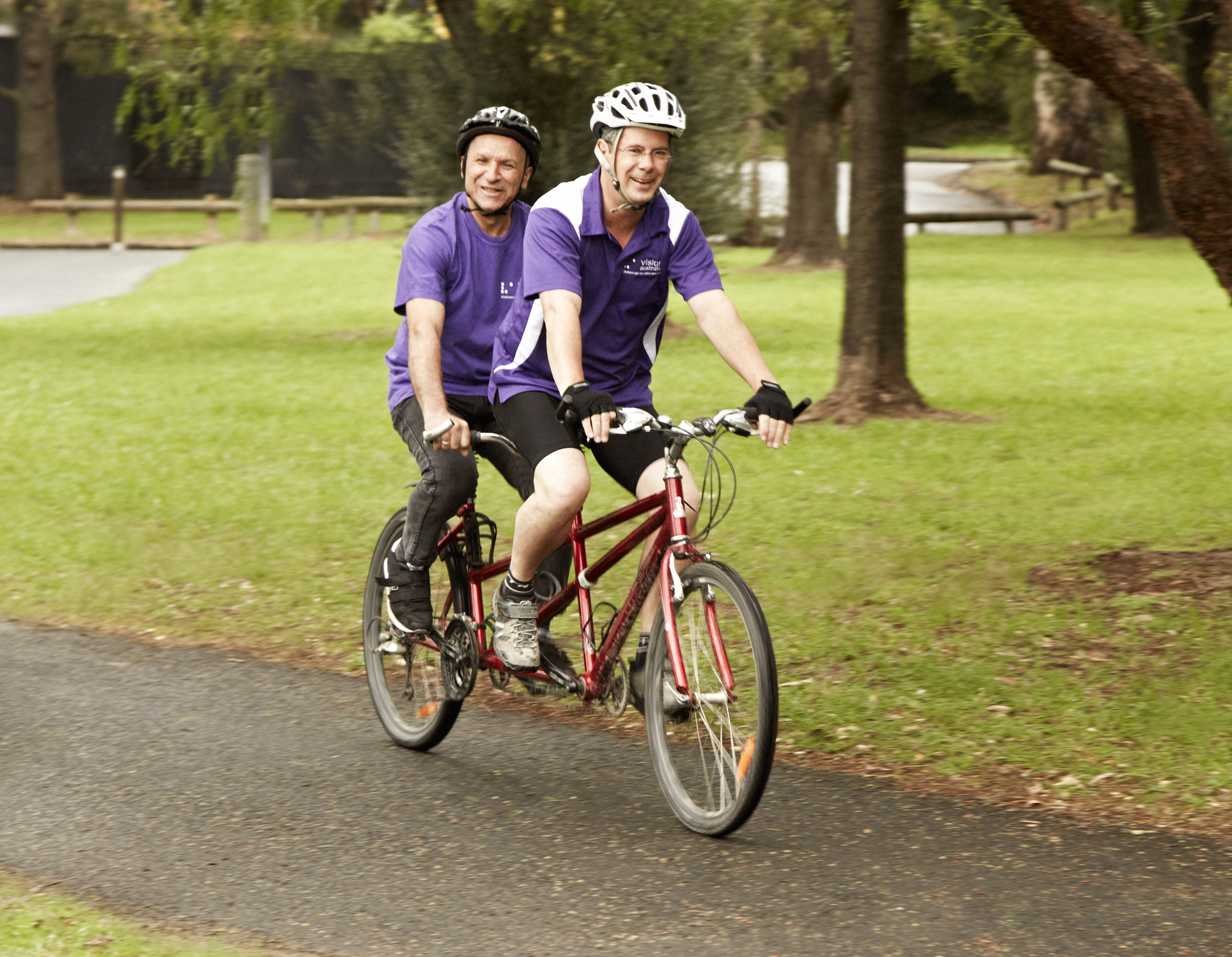 A volunteer and man who is blind cycling on a tandem bike