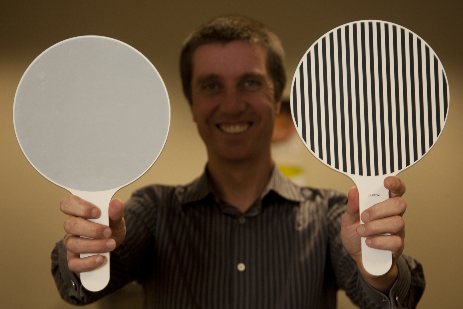 Man holds up two paddles, one is striped and the other is grey.