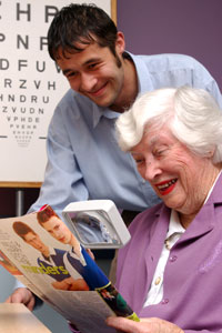 Woman being shown how to use a magnifier