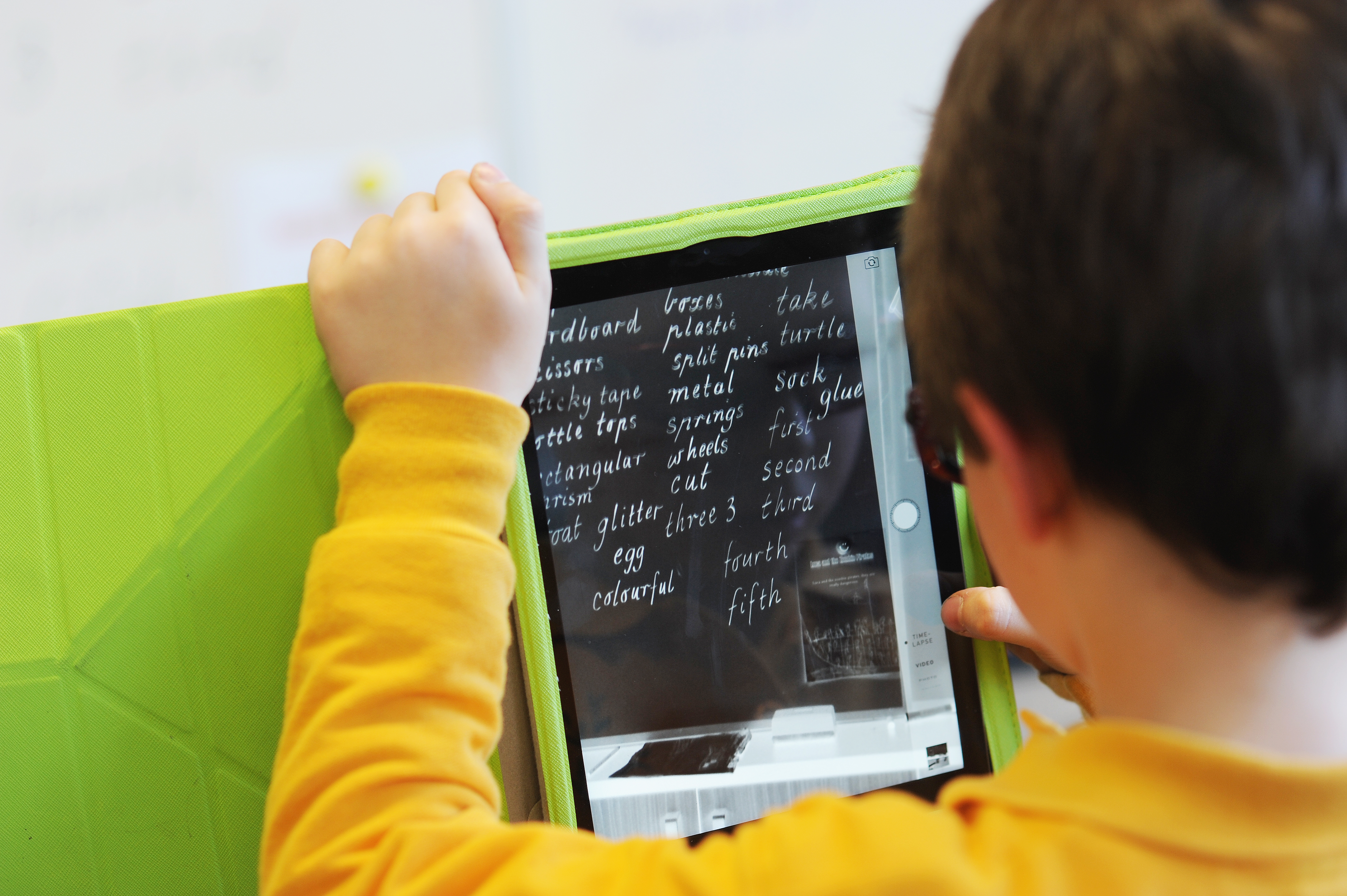 Boy using a tablet with magnification, he is looking at his weekly spelling words